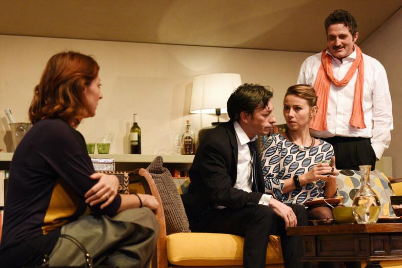 """Una scena della commedia francese """"Le prénom"""", portata in scena dallo Stabile di Genova. Un uomo e una donna stanno parlando seduti sul divano, con un'aria interdetta. Li guardano divertiti altri due amici"""
