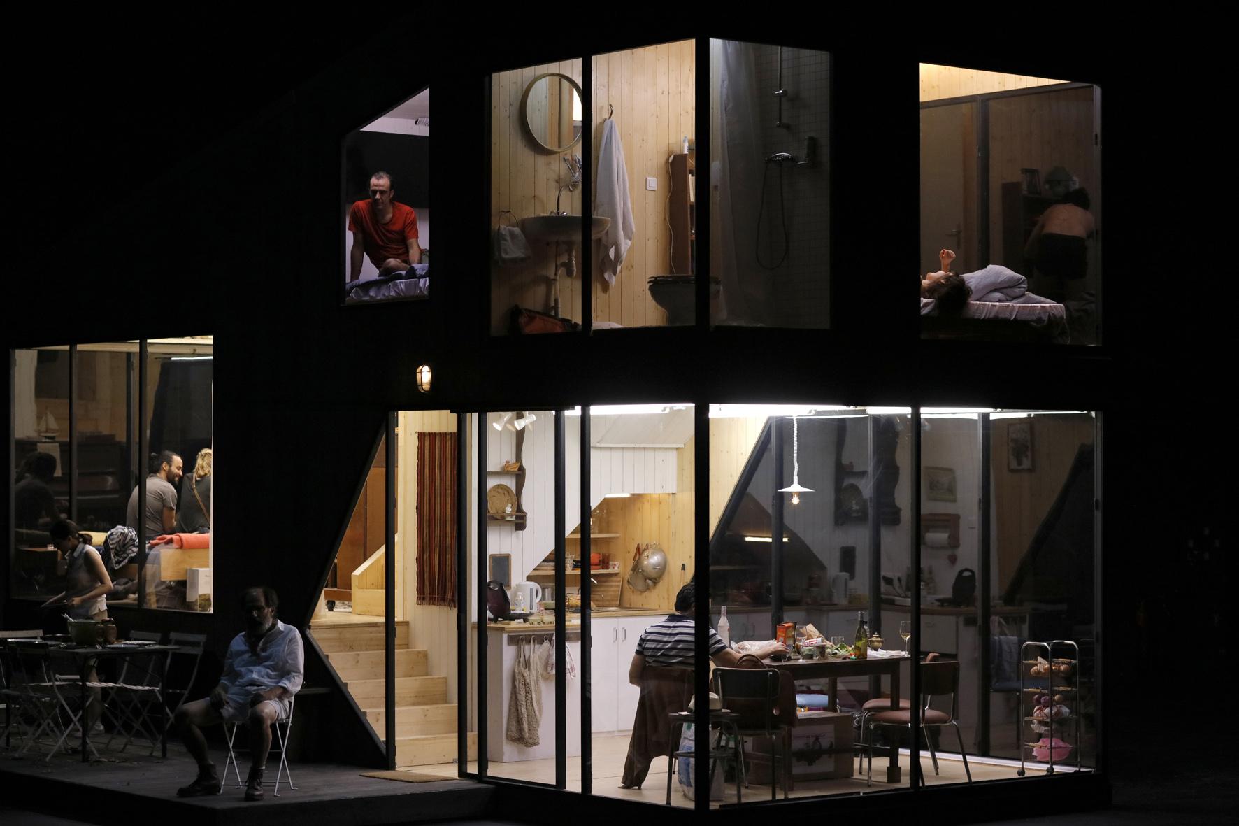 Immagine panoramica della casa a due piani rotante allestita in scena, nelle cui stanze recitano gli attori