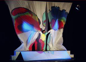 """Una scena dello spettacolo """"Di segno in segno"""" nella quale l'attrice affera due lenzuola bianche sulle quali sono disegnate ali di farfalla variopinte"""