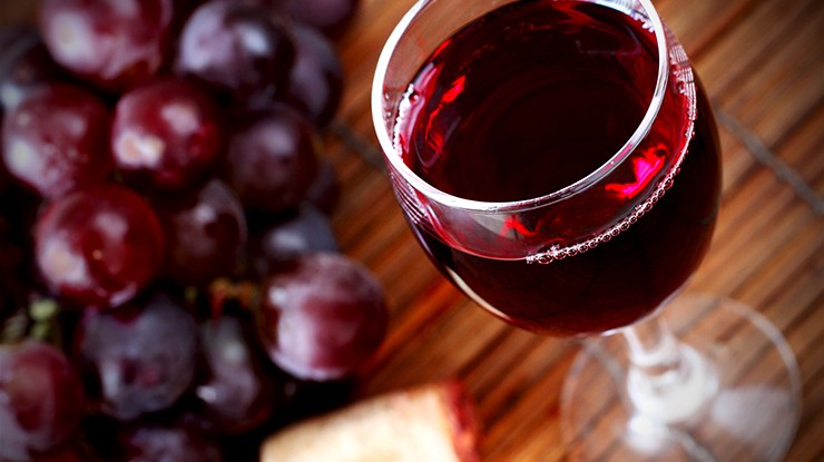 Grappolo e bicchiere di vino rosso