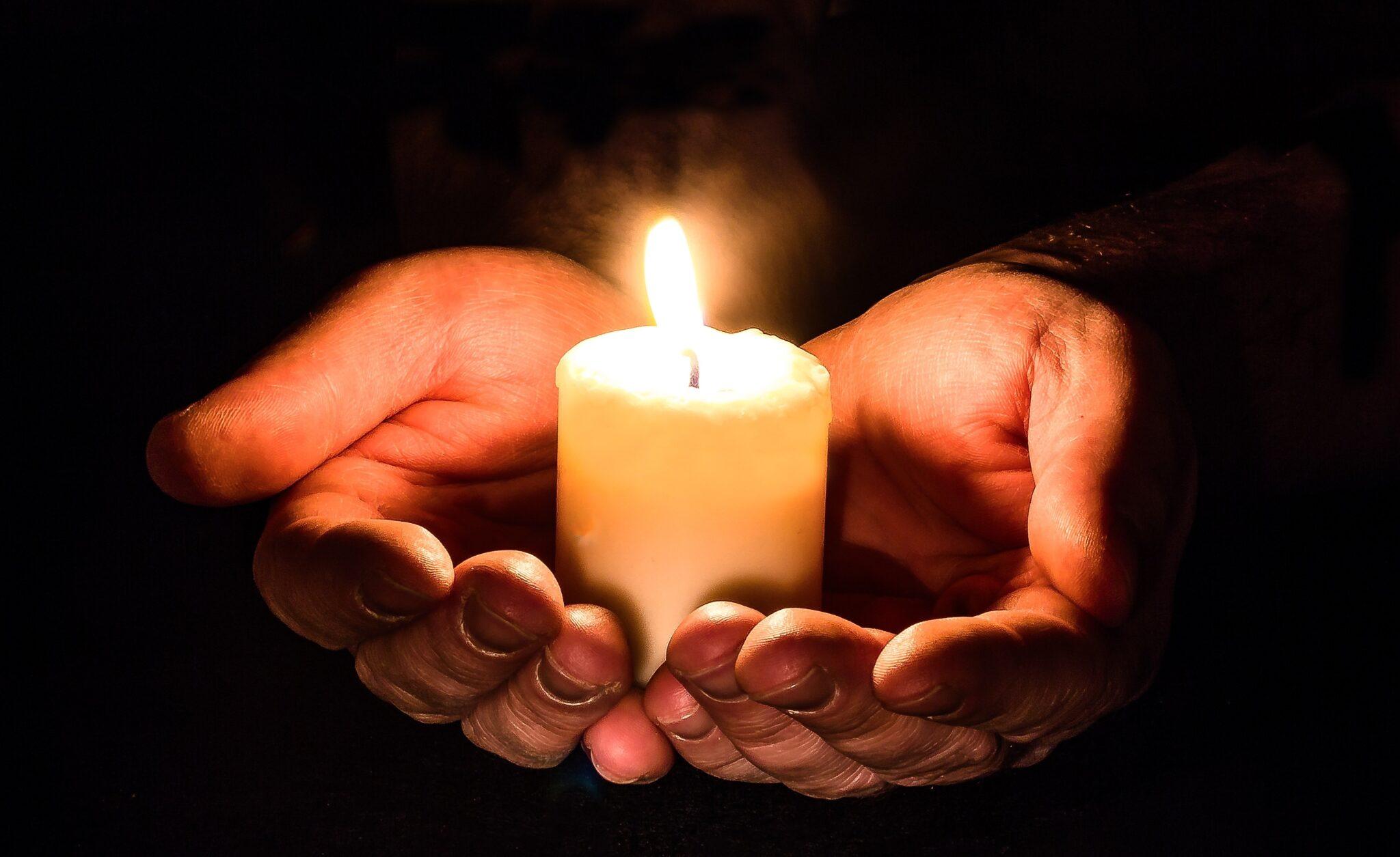 Due mani tengono una candela accesa