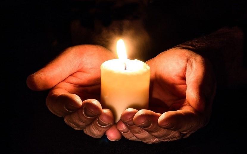 Due mani reggono una candela accesa